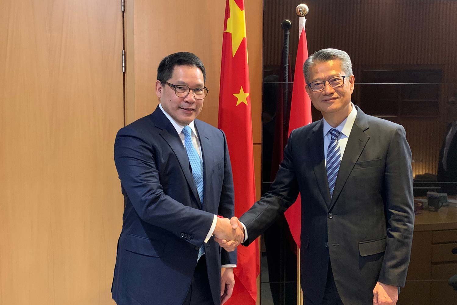 Finance Minister Uttama Savayana, left, meets Hong Kong Financial Secretary Paul Chan in Hong Kong on Monday. (Photo from the Fiscal Policy Office)