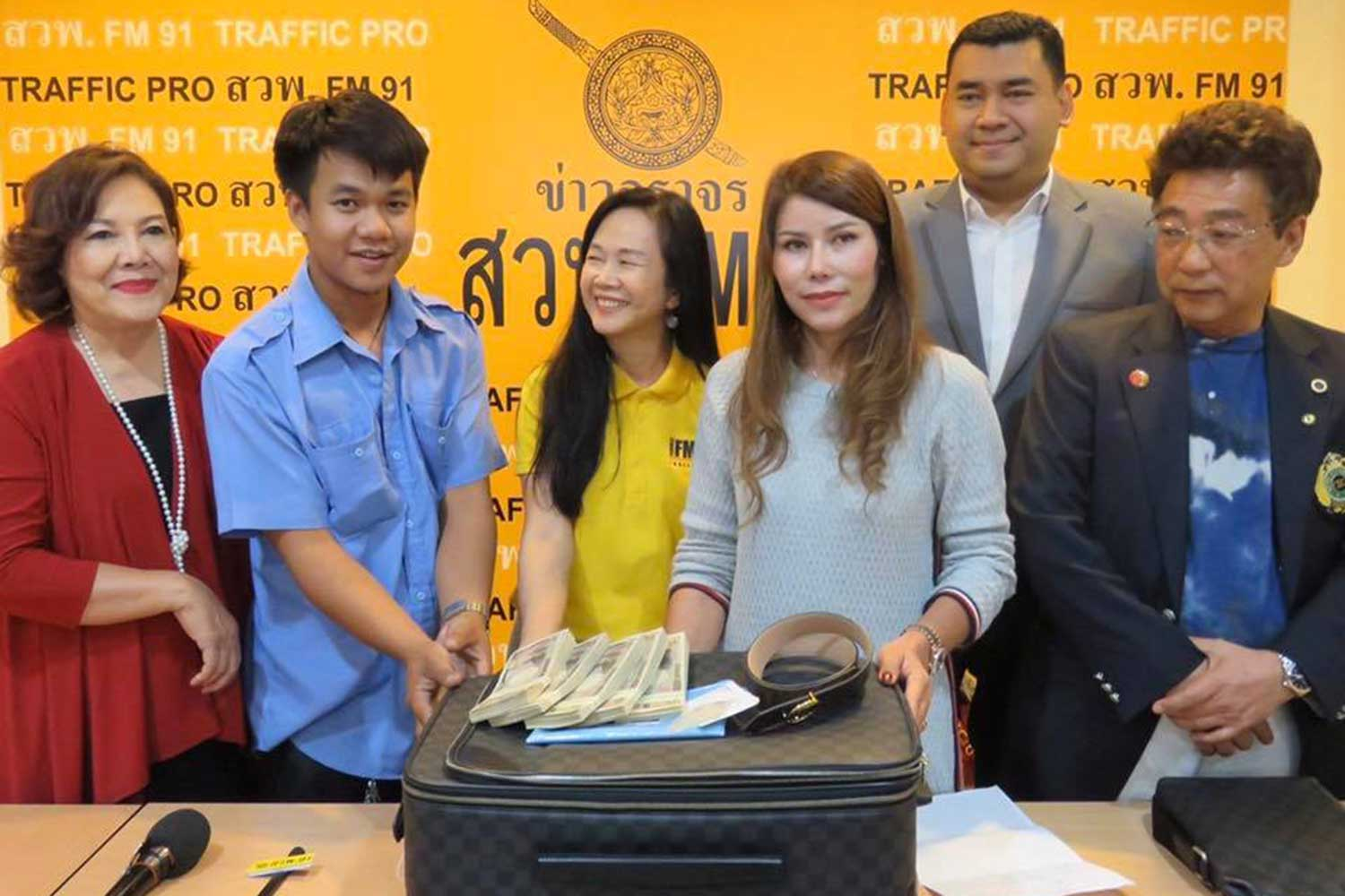 Withoon Jungphan, 22, second from left, returns cash and valuables worth about 1.5 million to a Thai businesswoman who left her bag at his cab. The handover was witnessed by executives of FM91 traffic radio station on Tuesday afternoon. (Photo taken from @fm91trafficpro Facebook page)