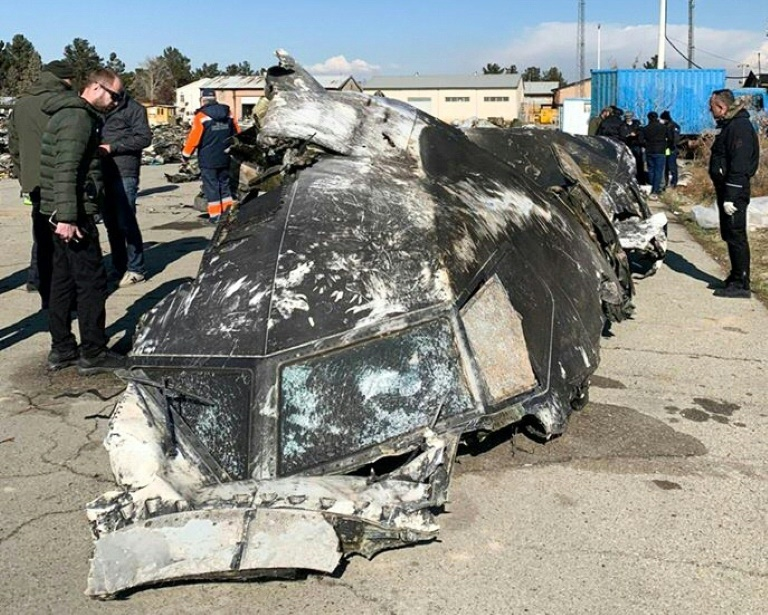 People analyze the fragments and remains of the Ukraine International Airlines plane that crashed outside Tehran.