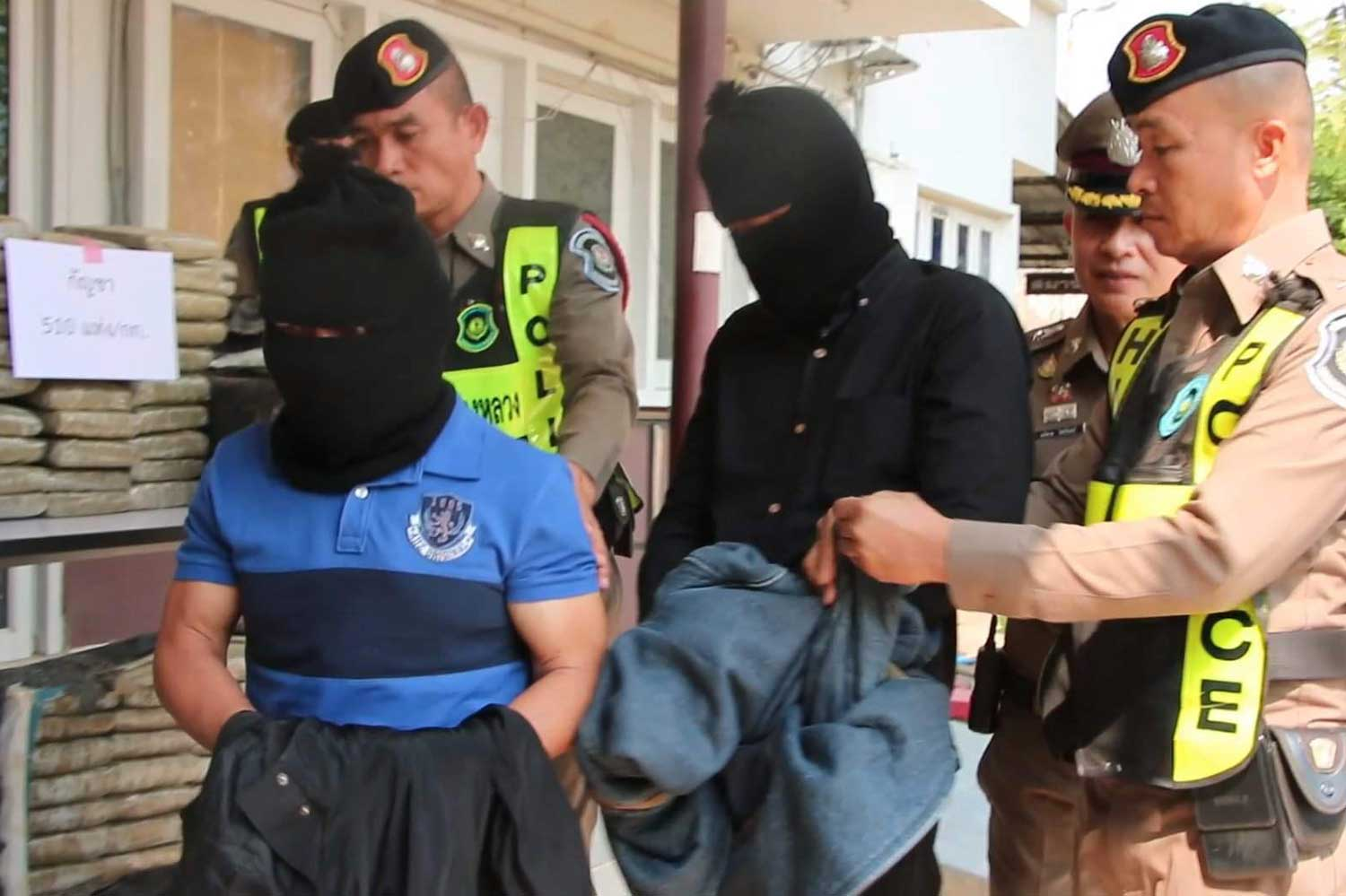 Two of three people arrested for involvement in the smuggling of marijuana are escorted by highway police for a media briefing in Khon Kaen on Thursday. (Photo by Chakrapan Nathanri)