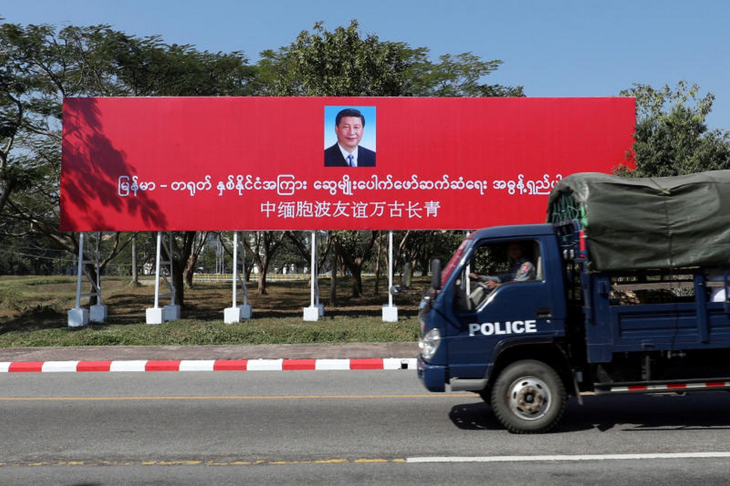 A police van drives by a banner welcoming Chinese President Xi Jinping ahead of his visit to Myanmar, in Nay Pyi Taw. (Photo: Reuters)