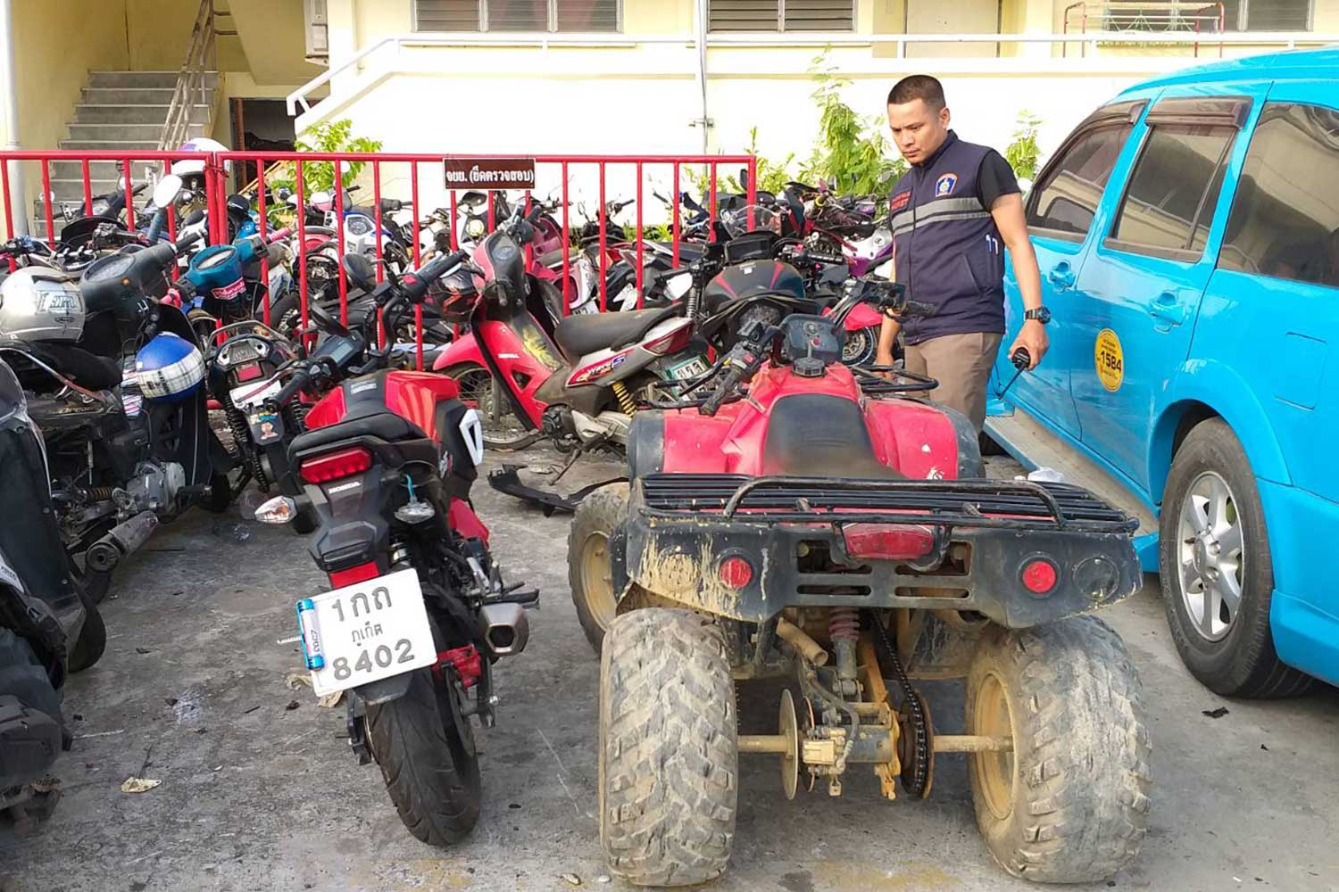 A police officer examines the red all-terrain vehicle (ATV) involved in a crash with a motorcycle that caused the death of an elderly Frenchman in Muang district, Phuket. (Photo by Achadtaya Chuenniran)