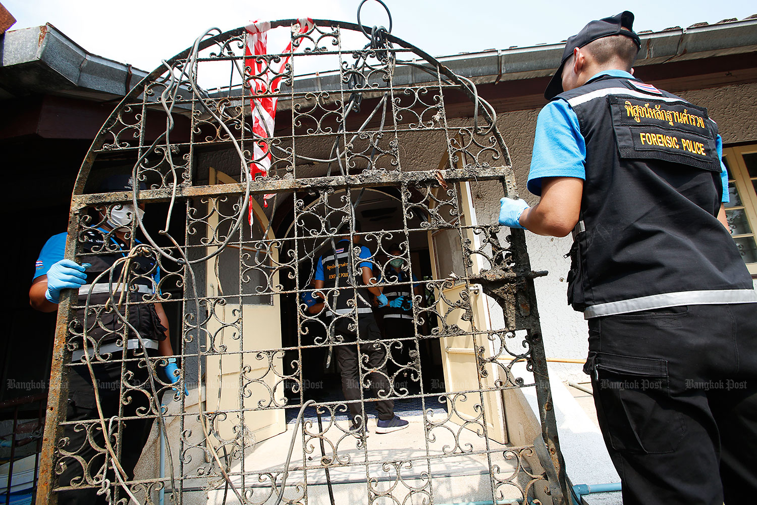 Forensic police carry a metal gate retrieved from a pond to fit to a door of a house owned by murder suspect Apichai Ongwisit, 40, in Bang Khae district. They believed the suspect used the gate to weigh down at least one body dumped in the pond near the house. (Photos Pornprom Satrabhaya)