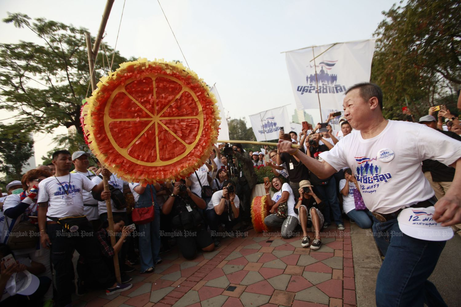Maj Gen Rienthong Nanna, the owner of Mongkutwattana General Hospital, hits a large mock-up of an orange — the colour of the Future Forward Party — during a run held to support Prime Minister Prayut Chan-o-cha at Lumpini Park on Jan 12. (Photo by Pornprom Sattrabhaya)
