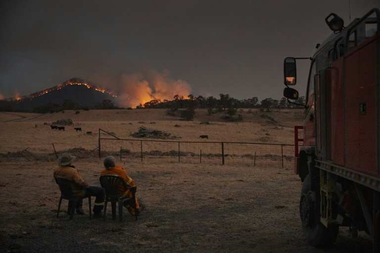 Volunteer firefighters watch as a bushfire rages on the outskirts of the town of Tumbarumba in New South Wales.