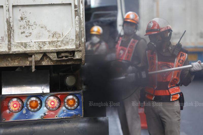 Traffic police check exhaust fumes released by lorries in Don Muang district on Thursday after the capital is hit by smog. (Photo by Pornprom Satrabhaya)