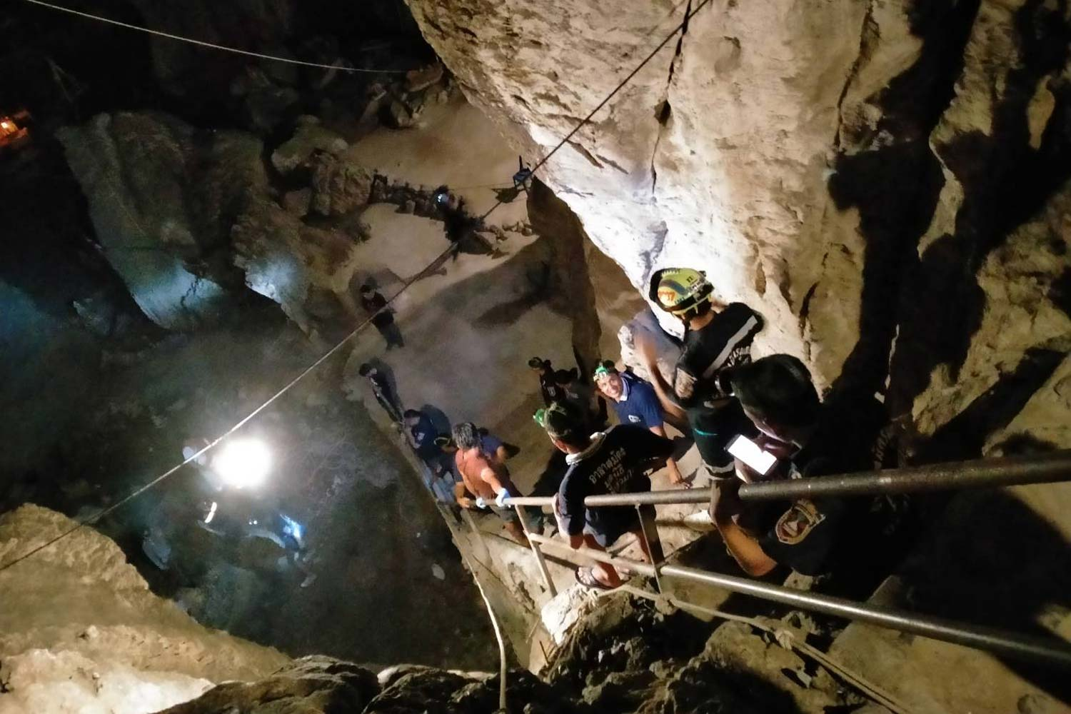 Rescuers descend a staircase to the ground floor of Tham Takfa cave in Nakhon Si Thammarat's Phrom Khiri district, where a monk was found dead after a fall on Sunday. (Photo by Nujaree Raekrun)