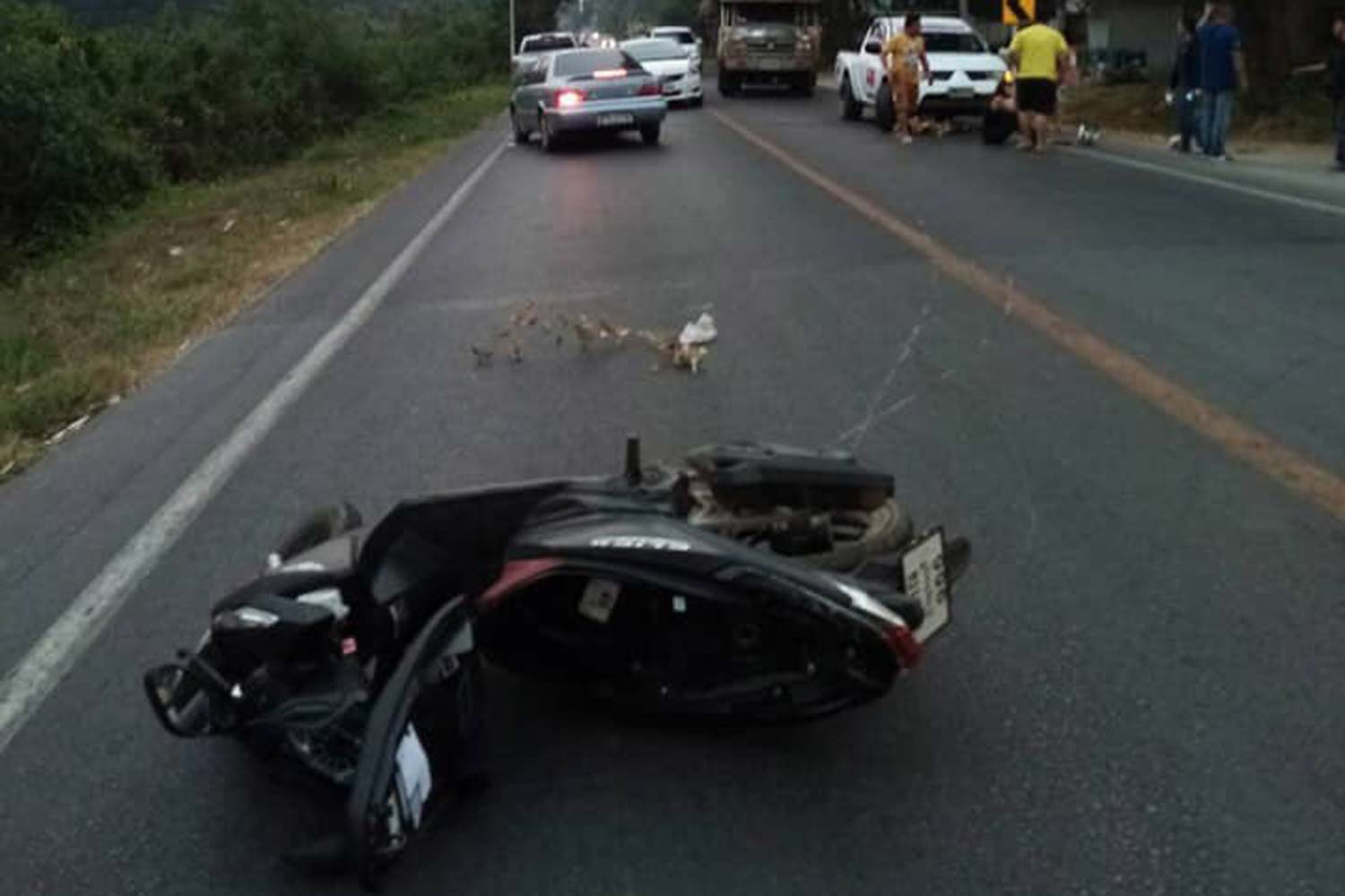 The tourists' motorbike is left lying on the Kanchanaburi-Dan Ma Kham Tia road in Kanchanaburi's Muang district after the two women were swept off it by a cable hanging  across the road at neck level on Sunday. (Photo by Piyarat Chongcharoen)