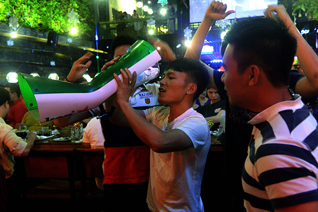 A man drinks beer from a tower as his friends look on at a local open-air beer bar in downtown Ho Chi Minh City in 2015. (AFP file photo)