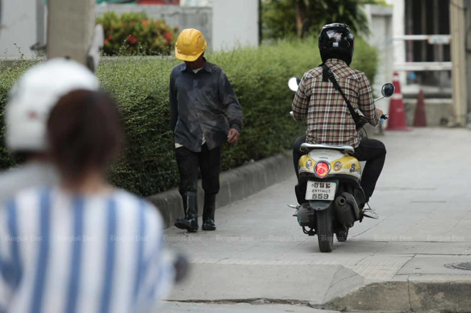 A motorcyclist rides on a footpath near Lamsalee intersection, a traffic hotspot in the Ramkhamhaeng area, to avoid congestion on Ramkhamhaeng Road. City Hal has collected more than 21.5 million baht in fines from thousands of motorcycle riders who ignored laws and rode on pavements. (File photo)