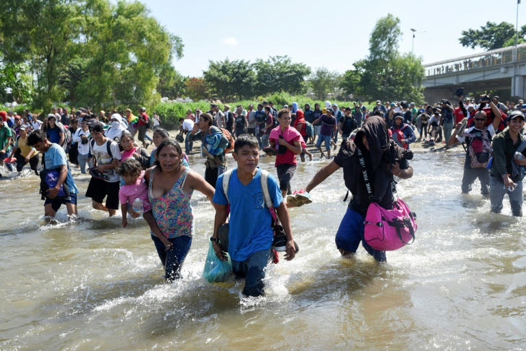 Central American migrants -- mostly Hondurans travelling in a caravan to the US -- cross the Suichate River between Guatemala and Mexico, where Mexican forces fired tear gas trying to force them back.