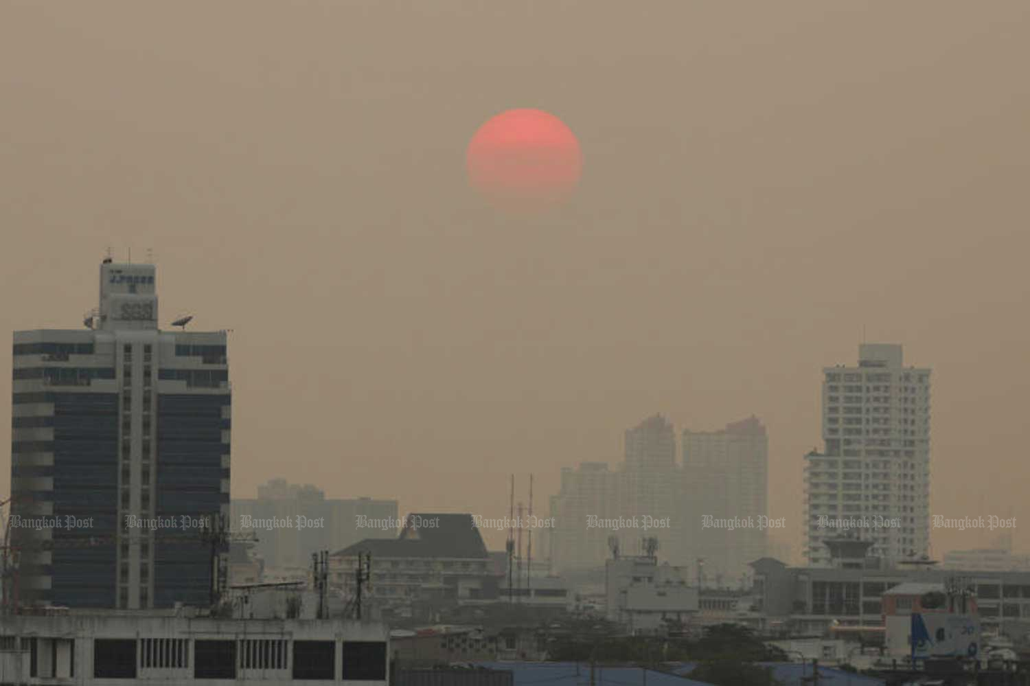 The sun sets in Bangkok sky shrouded by thick smog on Tuesday evening. (Photo by Nathaphol Lovakit)