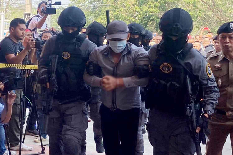 Police commandos escort robbery-murderer suspect Prasittichai Khaokaew, 38, into the tourist police office in Lop Buri province on Wednesday. (Police photo)