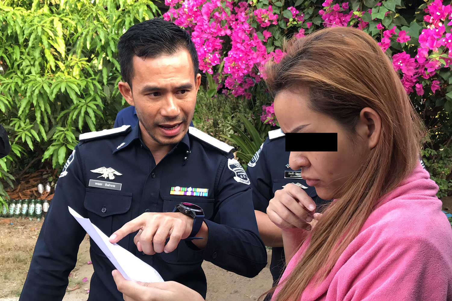 """Chuthathip """"Manao"""" Nimnuan, a key recruiter for the Mae Manee Ponzi scheme, reads a document as Department of Special Investigation officers search her house in Ratchaburi on Wednesday. (Photo taken from Department of Special Investigation @DSI2002 Facebook page)"""