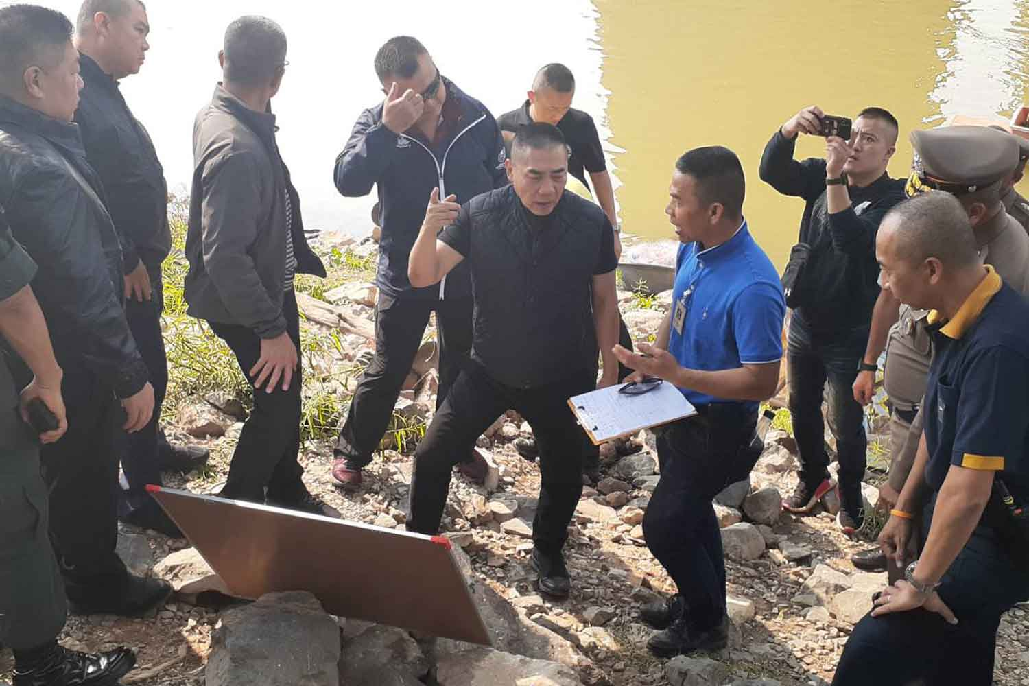 National police chief Pol Gen Chakthip Chaijinda, centre, directs the fruitless search for the stolen gold from the bank of the Chao Phraya river in Sing Buri province on Wednesday. (Police photo)