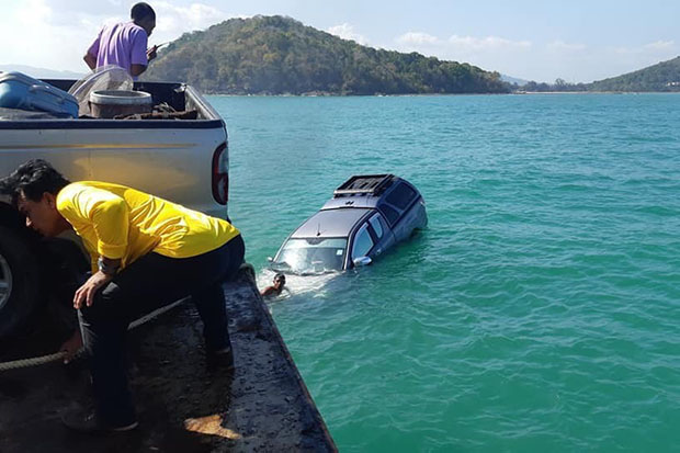 Crew members try unsuccessfully to salvage the floating pickup truck after it slid off the ferry boat Koh Yao Centre and into the Andaman Sea on Wednesday. The vehicle defied their efforts and sank. (Photo by Achadtaya Chuenniran)