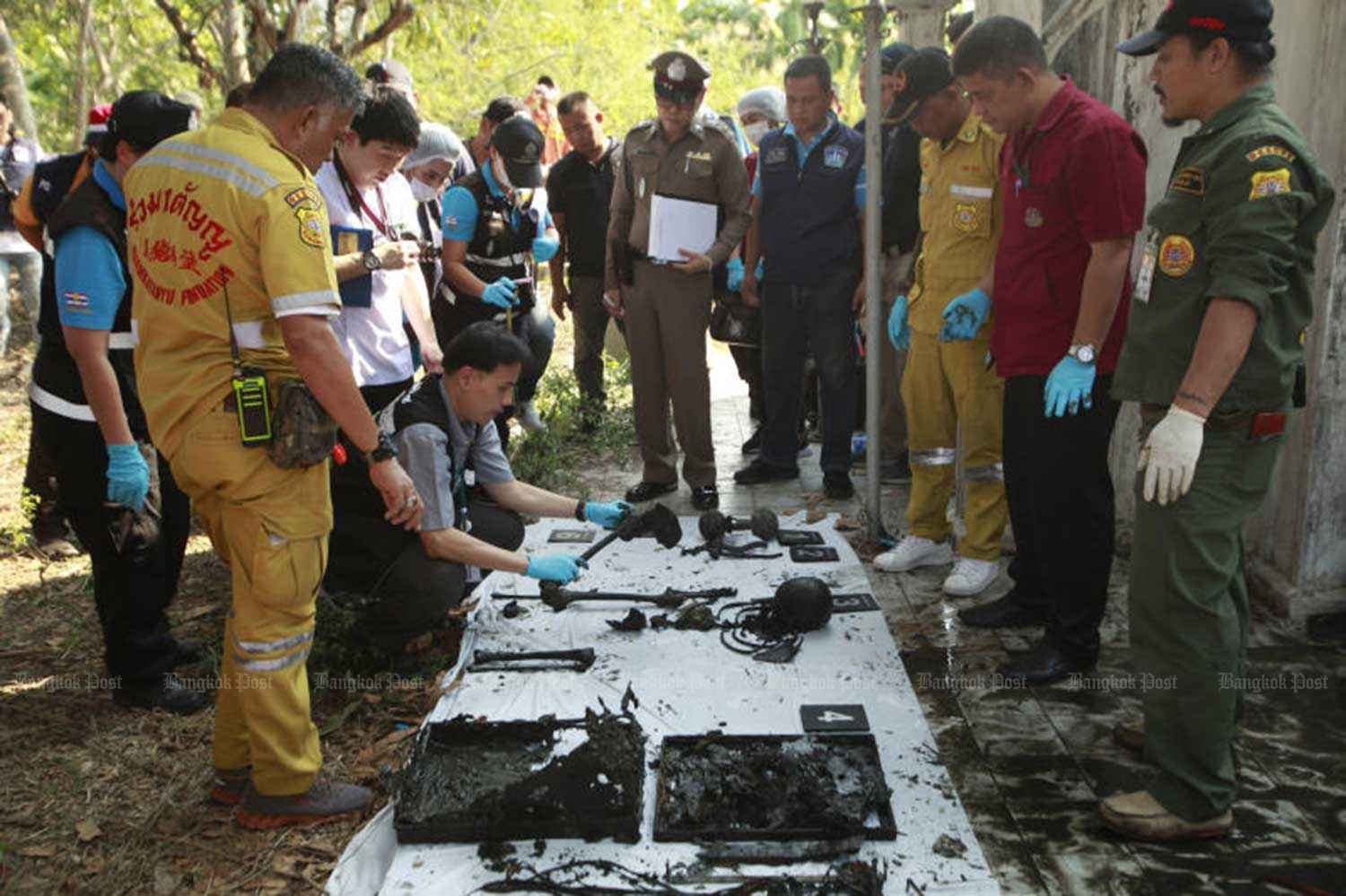 At least 30 human bones and a skull are found in an old metal casket in a pond at the home of a 40-year-old murder suspect in Bangkok's Bang Khae district. The man was earlier charged with killing a 22-year-old woman and concealing her corpse. (Photo by 