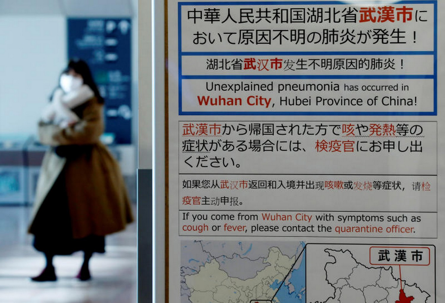 A woman wearing a mask walks past a quarantine notice about the outbreak of coronavirus in Wuhan, China at an arrival hall of Haneda airport in Tokyo on Monday. (Reuters photo)