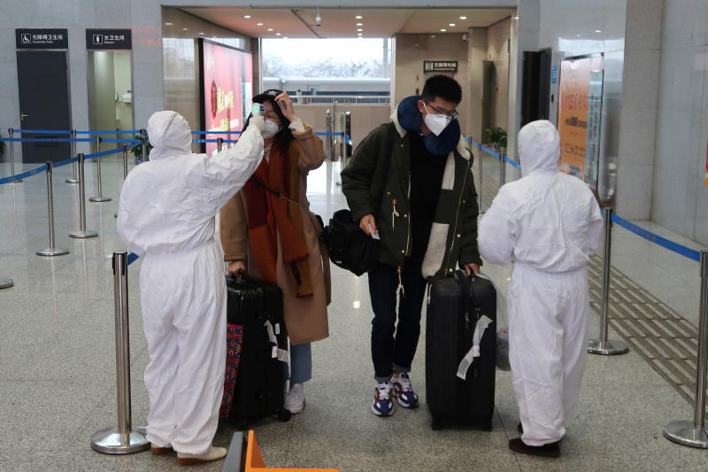 Workers in protective suits check the temperature of passengers arriving at the Xianning North Station in Xianning, a city bordering Wuhan to the north, in Hubei province, on Friday. (Reuters photo)