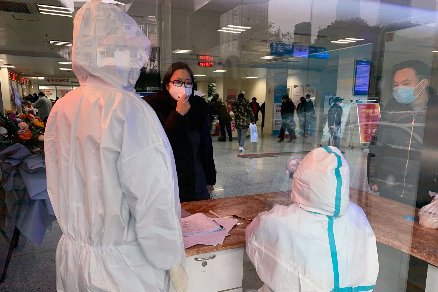 A woman wearing a face mask speaks to hospital personnel wearing protective medical gowns at No.5 Hospital in Wuhan, China, on Friday. (Chris Buckley/The New York Times)