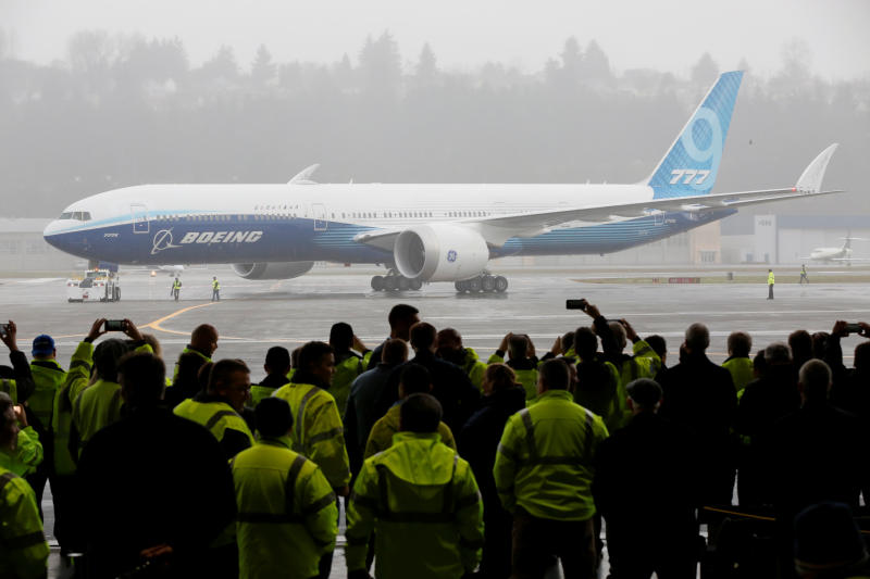 Boeing employees and others watch a Boeing 777X airplane return to a hangar after its first test flight at the company's facility in Seattle on Saturday. (Reuters photo)