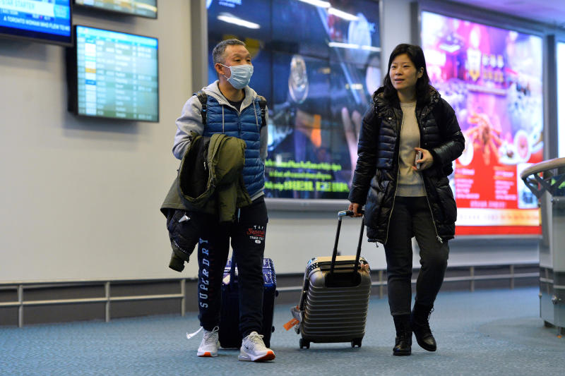 A traveller wears a mask after arriving on a direct flight from China , as Canada's Public Health Agency tries to prevent any introduction of coronavirus at Vancouver airport in Richmond on Friday. (Reuters photo)