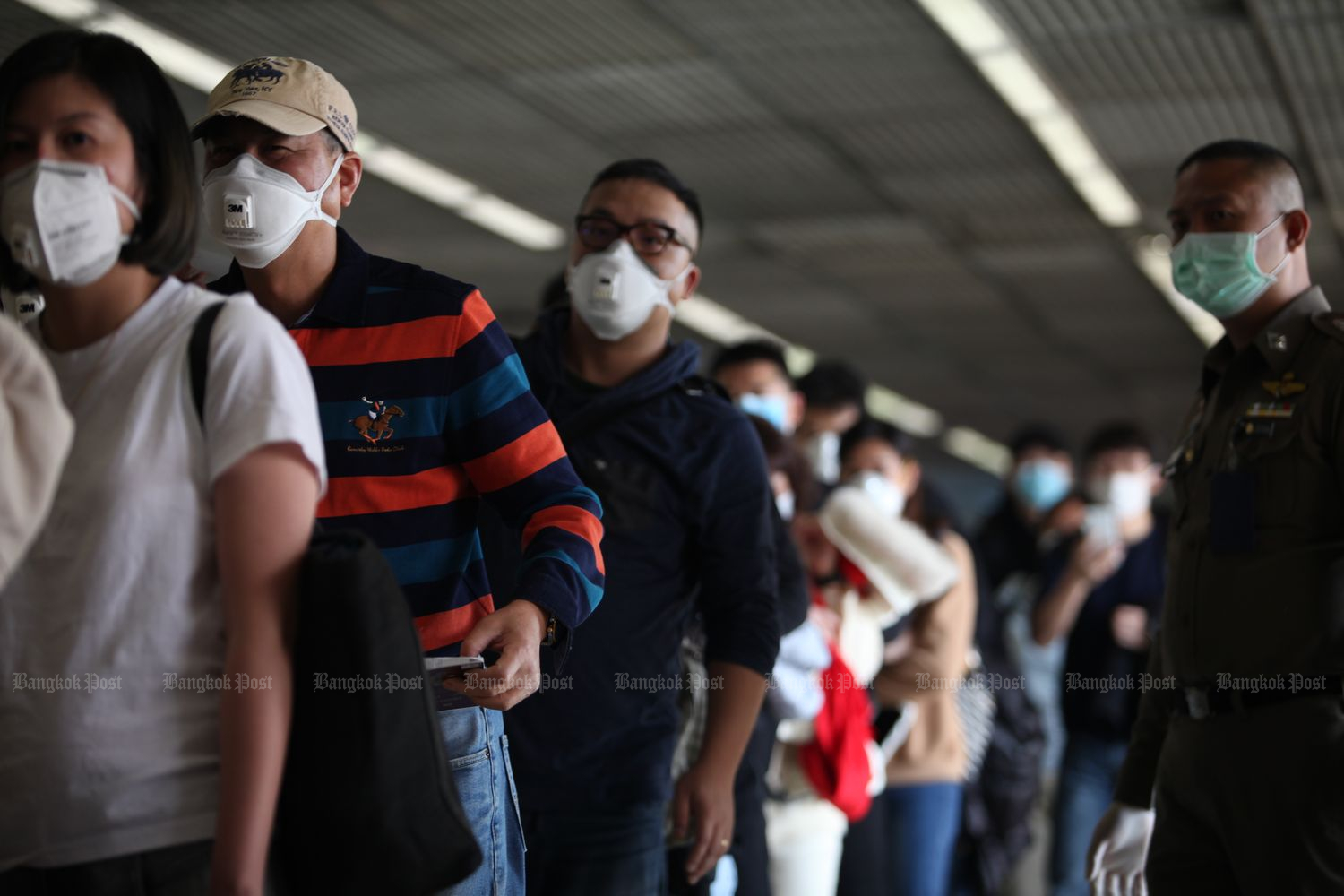 Tourists queue for a fever secreening at Don Mueang airport in Bangkok on Saturday. (Photo by Apichart Jinakul)