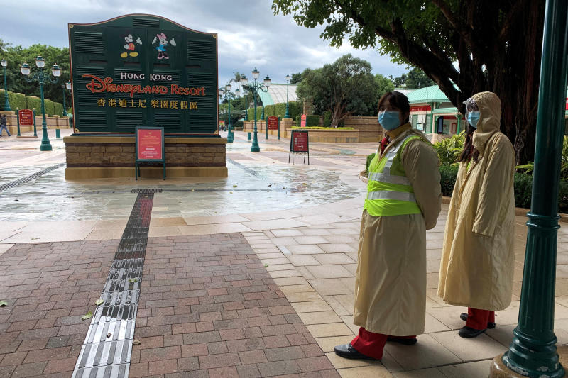 Employees wearing protective masks stand outside the Hong Kong Disneyland theme park that has been closed, following the coronavirus outbreak, in Hong Kong on Sunday. (Reuters photo)