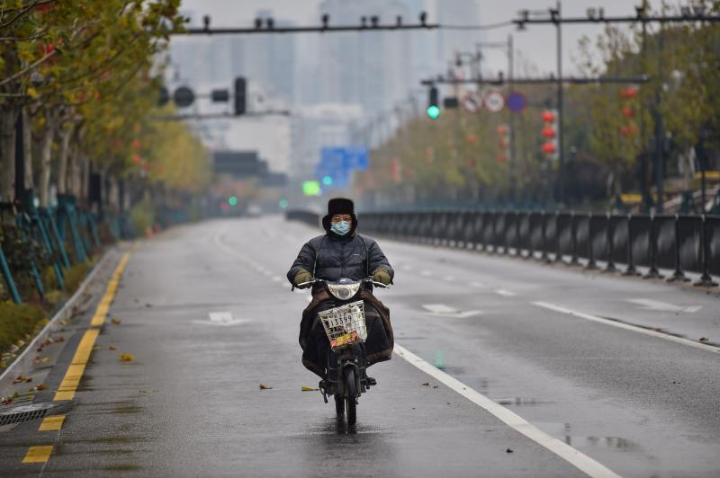 A man wearing a protective facemask rides a motorcycle on a street in Wuhan on Sunday. (AFP photo)