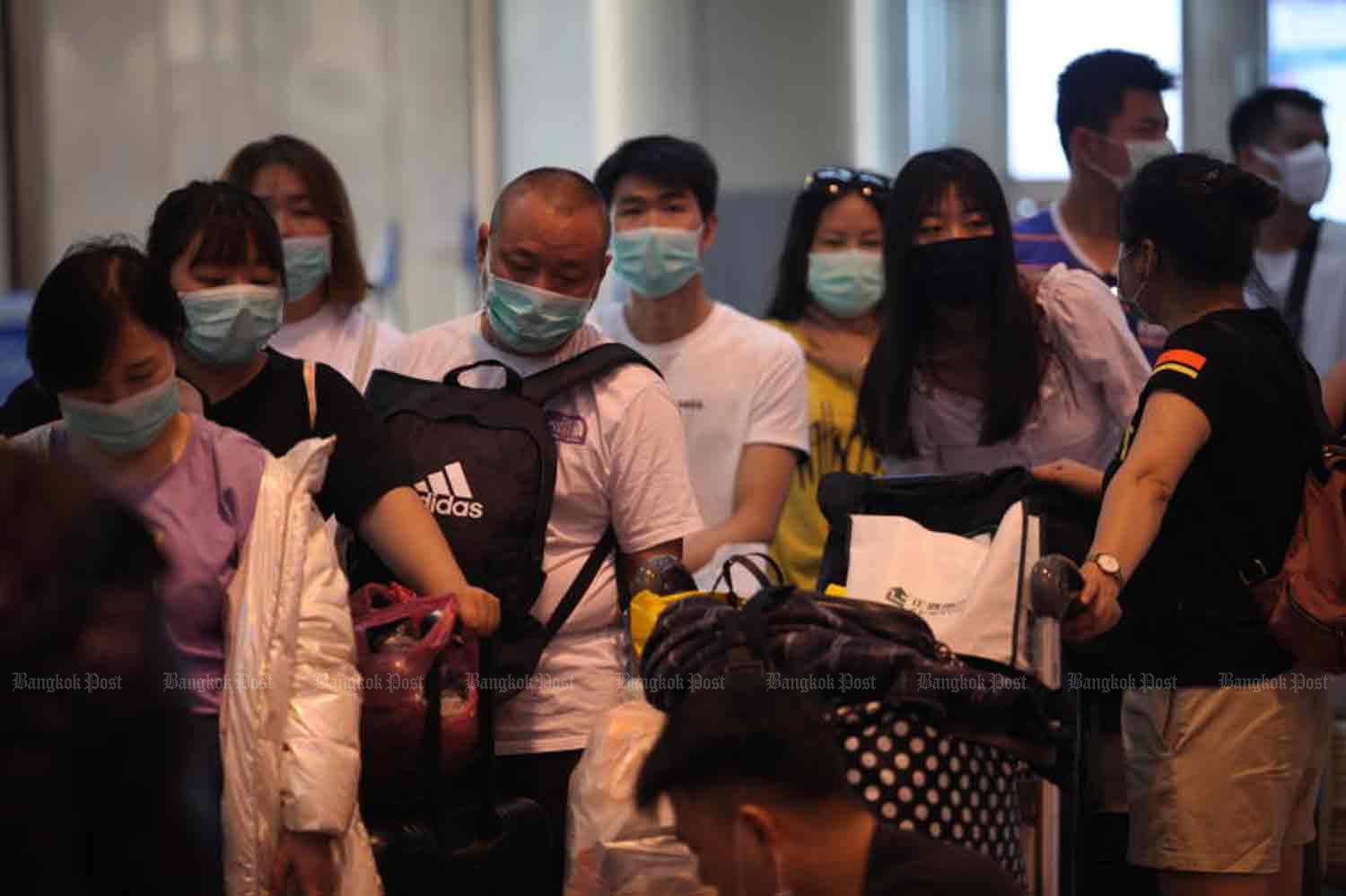 Tourists wear face masks at Don Mueang airport. Health officials are closely monitoring about 20,000 Chinese visitors here to celebrate Lunar New Year holiday, as the novel coronavirus from China continues to spread. (Photo by Apichart Jinakul)