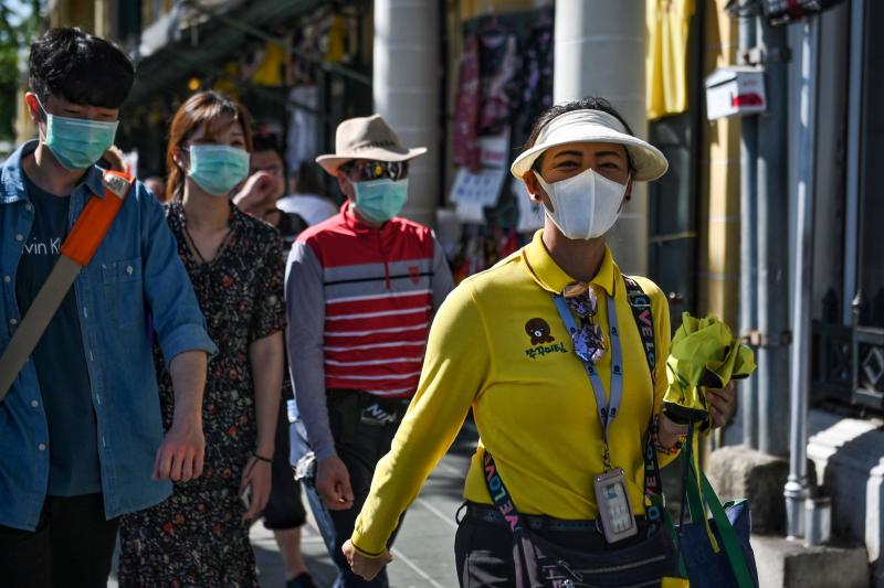 A Thai tour guide (right) escorts Chinese tourists wearing face masks near the Grand Palace on Monday. (AFP photo)