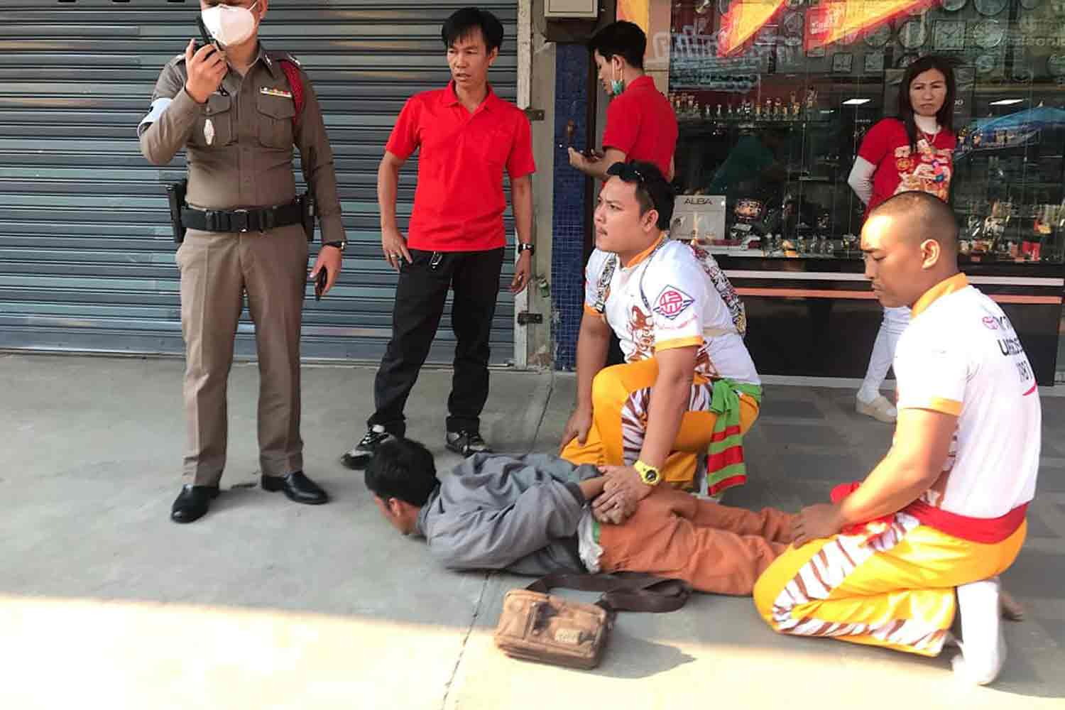 Members of a lion-dance troupe hold Preecha Inna firmly on the ground after he knocked over an elderly woman as he fled from a gold shop with two necklaces in Nakhon Sawan's Muang district on Monday. (Photo by Chalit Poomruang)