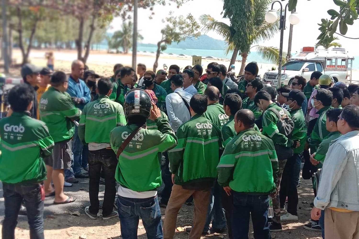 About 100 riders of app-based GrabFood food delivery service gather at Suphan Hin in Muang district of Phuket to demand a 10-baht increase in the delivery fee from the service operator. (Photo by Achadtaya Chuenniran)