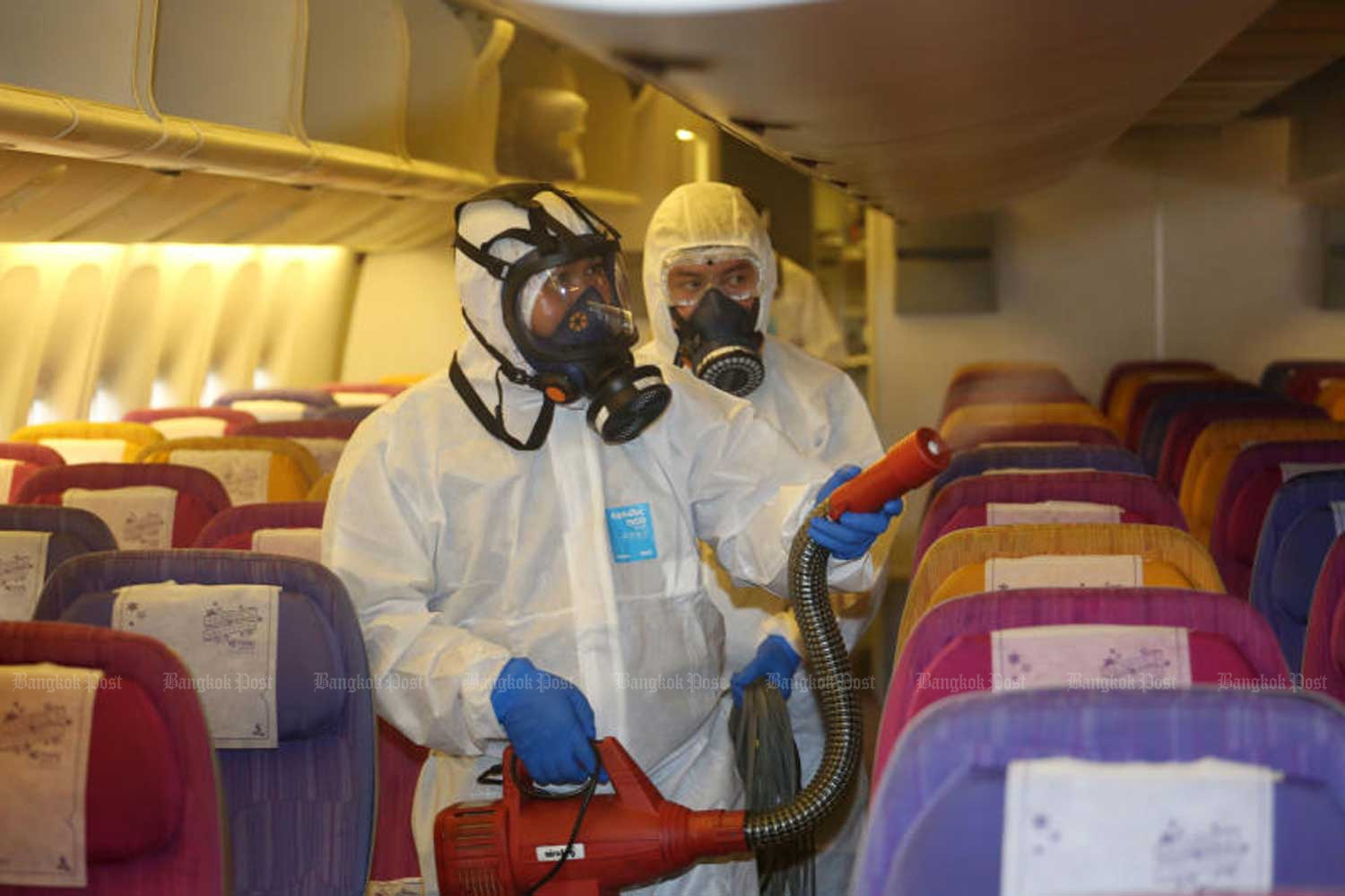 Workers disinfect the cabin of a Thai Airways International jet at Suvarnabhumi airport on Tuesday to prevent the spread of the deadly coronavirus. (Photo by Varuth Hirunyatheb)