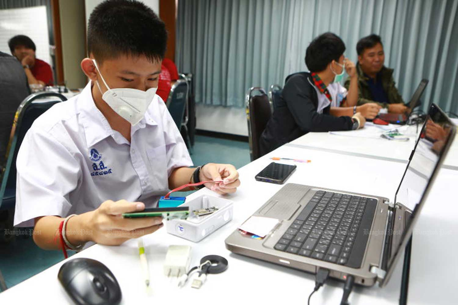 Students assemble fine-dust detectors to be distributed to schools affected by PM2.5 air pollution, during a workshop at the Engineering Institute of Thailand in Bangkok. (Photo by Somchai Poomlard)
