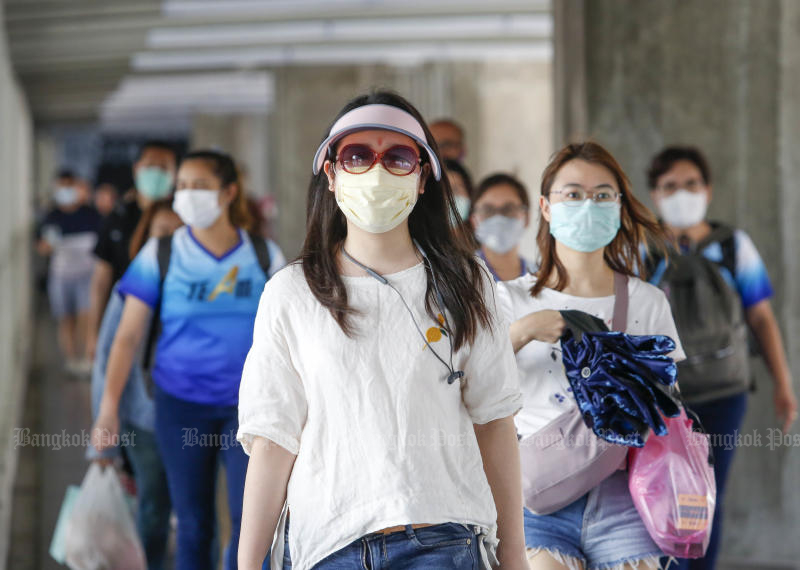 People wear face masks as they walked on the skywalk in Ratchaprasong area on Tuesday. (Photo Pattarapong Chatpattarasill)