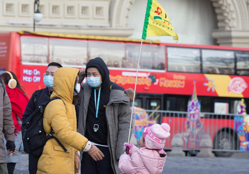 Tourists wear protective face masks as they walk in Red Square in Moscow on Monday. (Bloomberg photo)