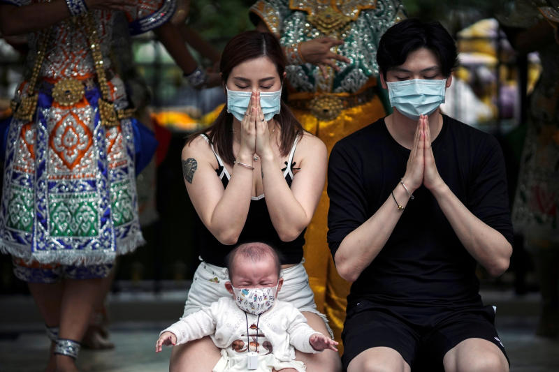 Chinese tourists wearing protective masks pray at the Erawan Shrine in central Bangkok on Thursday. (Reuters photo)