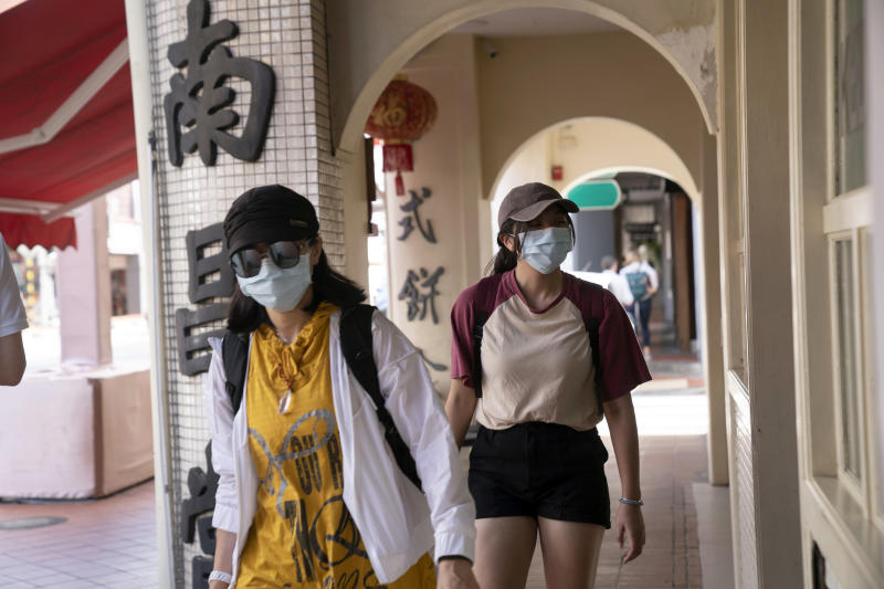 Pedestrians wearing protective masks walk through the Chinatown area of Singapore on Friday. (Bloomberg photo)