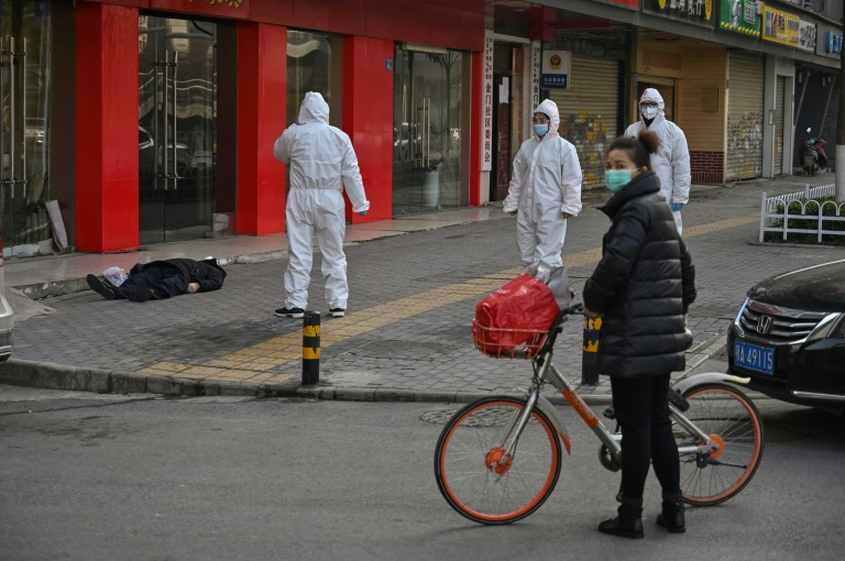 AFP reporters witness police and medics in protective suits dealing with a dead body in Wuhan.