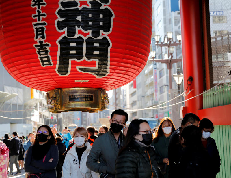 Tourists wearing protective masks walk past the Kaminarimon Gate as they visit Sensoji Temple in Tokyo on Friday. Japan is still a top destination for tourists from Thailand. (Reuters photo)