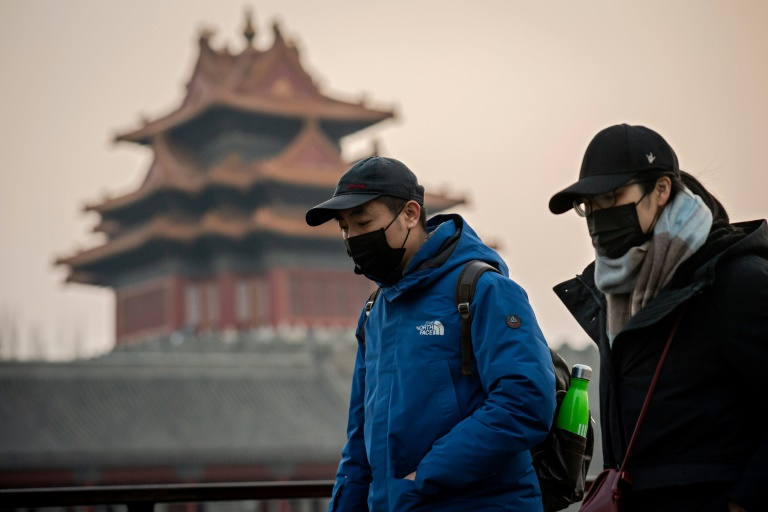 People wearing protective facemasks to help stop the spread of a deadly virus walk past the Forbidden City in Beijing.