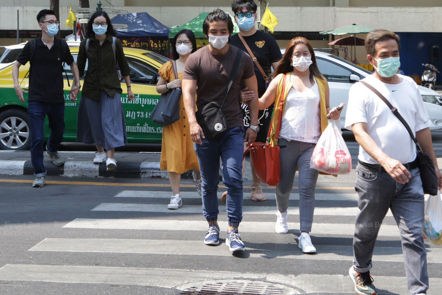 Tourists wear masks while shopping at the Ratchaprasong intersection in Bangkok on Saturday. (Photo by Apichit Jinakul)
