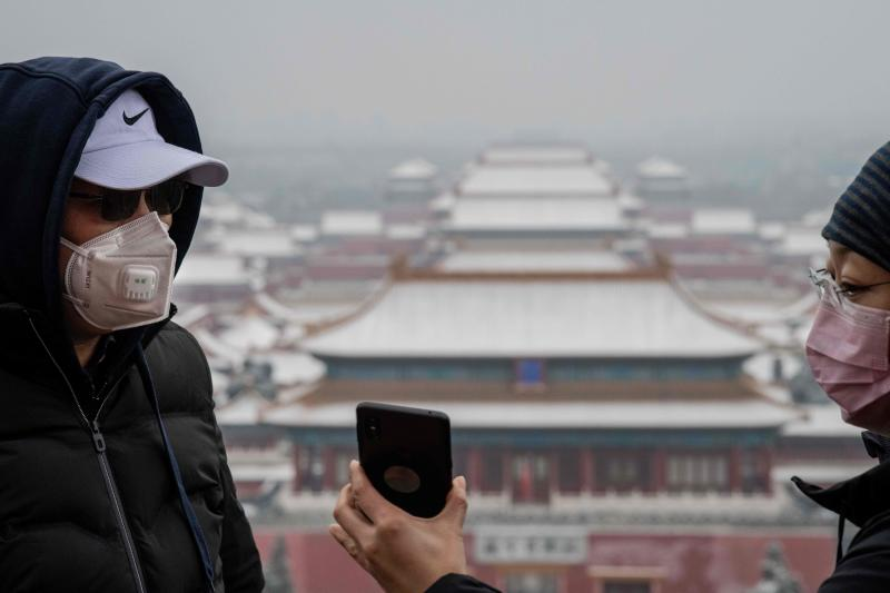 People wearing protective masks to prevent the spread of the SARS-like virus are seen from the Jingshan park overlooking the Forbidden city  after a snowfall in Beijing on Saturday. (AFP photo)