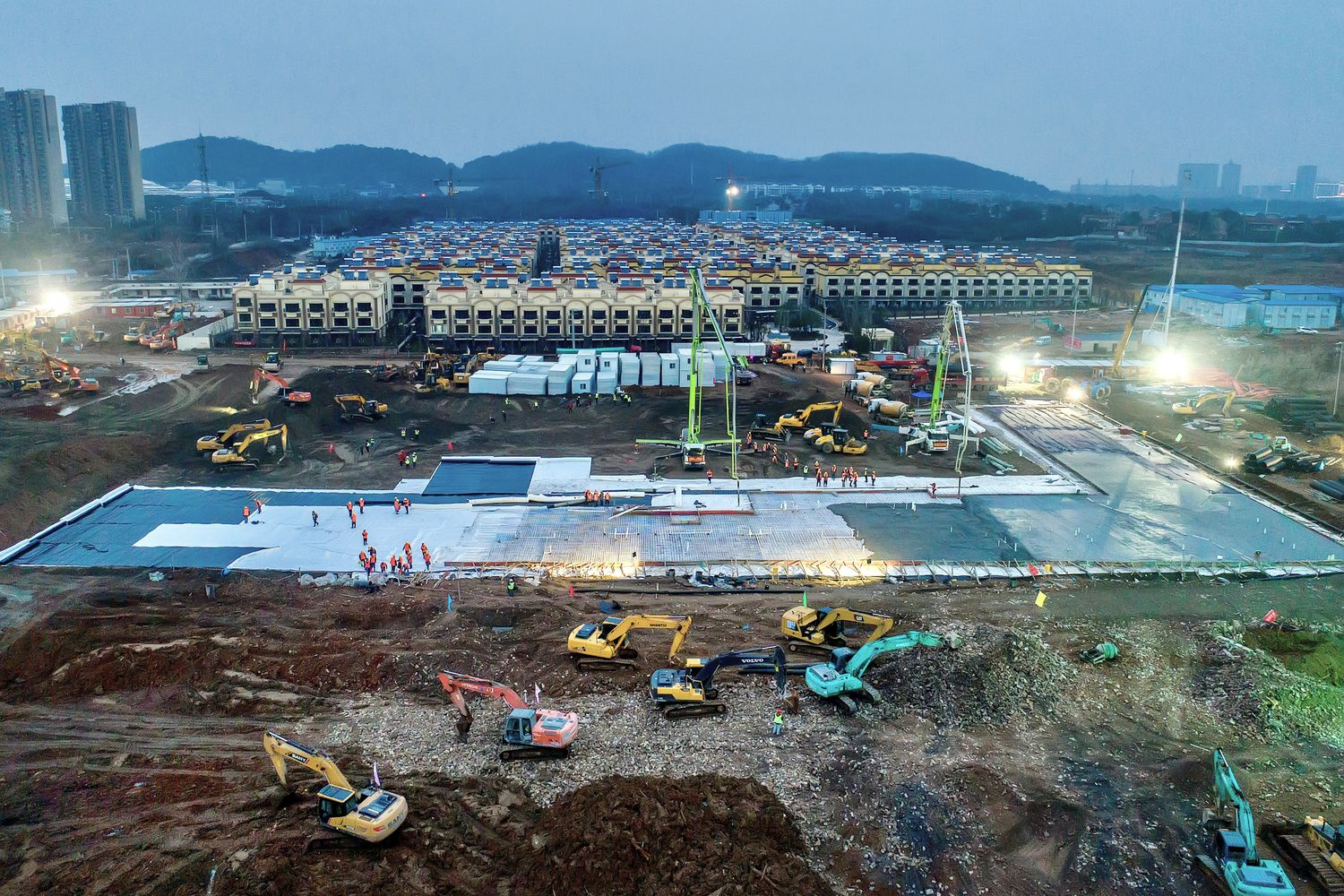 Excavators and workers are seen at the construction site where the new Huoshenshan Hospital is being built to treat patients of a new coronavirus on the outskirts of Wuhan on Jan 27. (China Daily via Reuters)