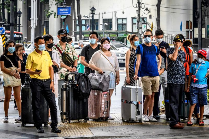 People with protective facemasks wait at a crossroad in downtown Bangkok on Monday. (AFP photo)