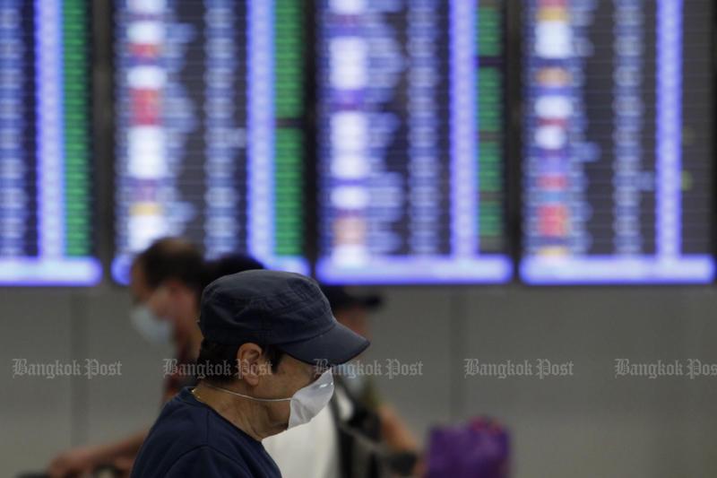 A tourist wearing a mask walks past a board displaying flights at Suvarnabhumi airport on Monday. (Photo by Wichan Charoenkiatpakul)