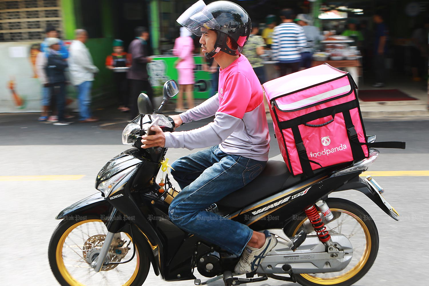 A food delivery man drives to pick up food after receiving an order via an app. He heads to a popular fried pork shop in the Klong Toey area where he places the food order before delivering it to his customer. (Photos by Somchai Poomlard)