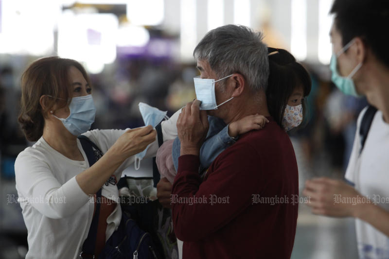Tourists wear face protective masks at Suvarnabhumi airport on Monday. (Photo by Wichan Charoenkiatpakul)