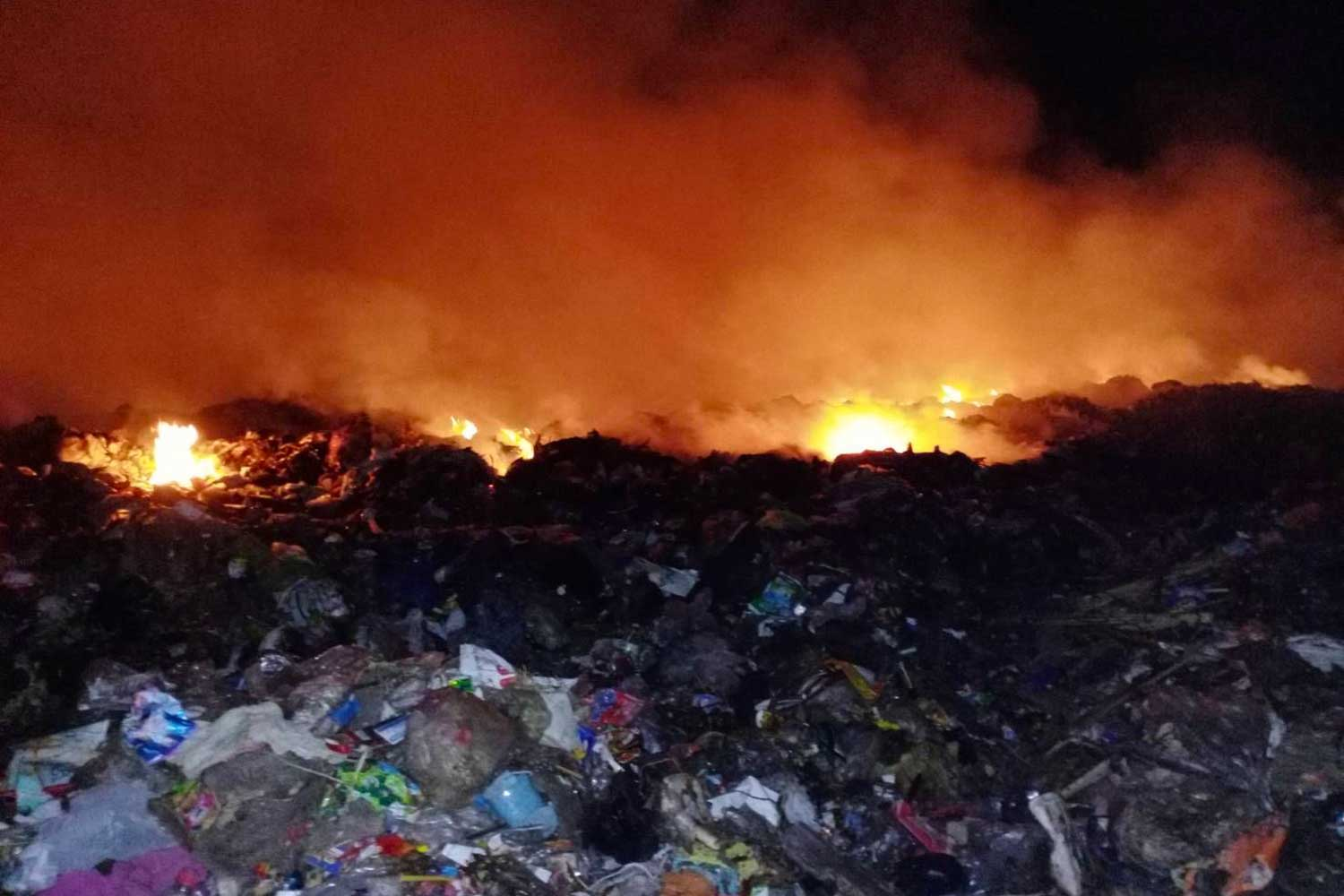 Fire and toxic smoke light up the night at the garbage dump in Nakhon Ratchasima's Pak Chong district overnight. (Photo by Prasit Tangprasert)
